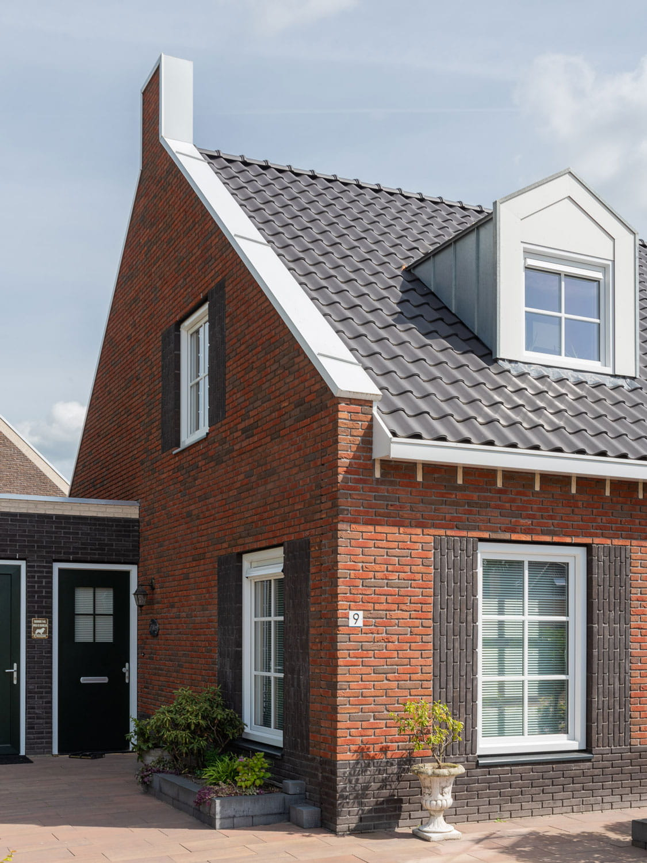 HOek van een huis met roodbruine steen en donkere dakpannen