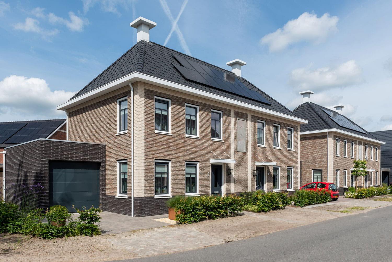 Een huis met lichte stenen en zwarte dakpannen