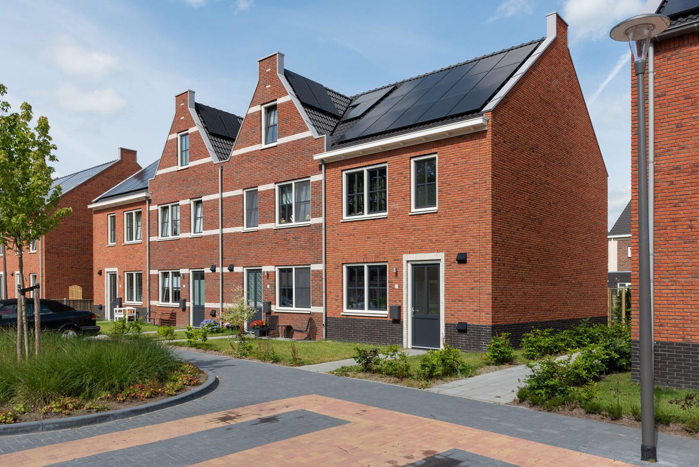 Een rij met huizen met rode bakstenen en donkere dakpannen met steeds een andere gevel
