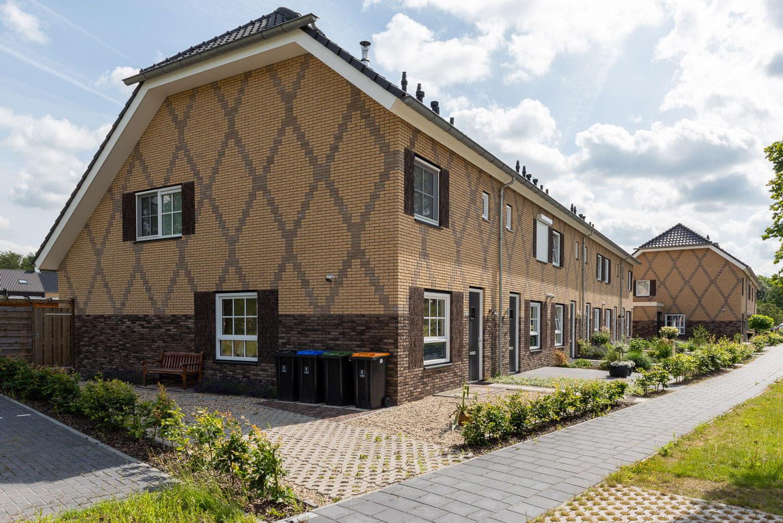 Rij met huizen met een lichtgele baksteen en kruizen in het metselwerk