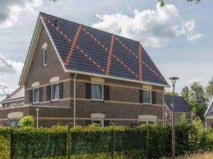 Huis met een dak waarbij de dakpannen een kruis hebben