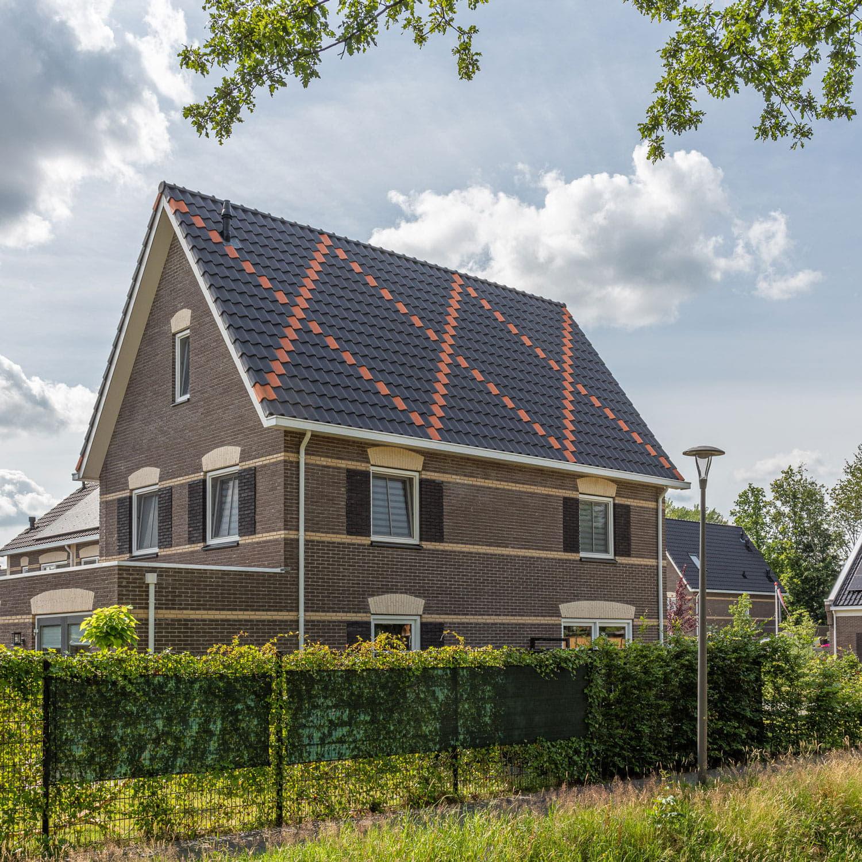 Vrijstaand huis met zwarte dakpannen waarin een kruis van oranje dakpannen zit