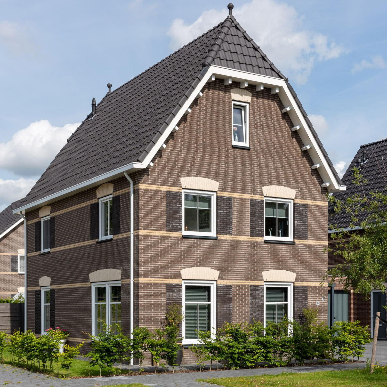 Vrijstaand huis met donkere gevelstenen en zwarte dakpannen