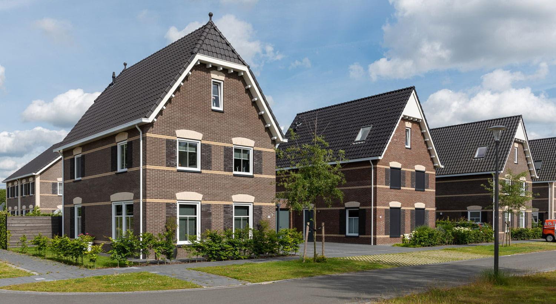 Twee vrijstaande huizen met donkere gevelstenen en zwarte dakpannen