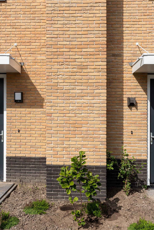 Detail van een muur met gelige gevelstenen en een bruine onderste rand