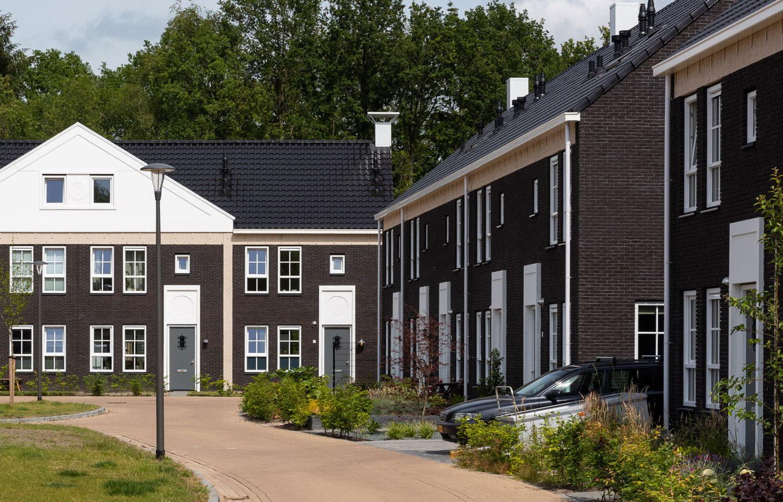 Een overzicht over woningen in een rij met een weg ervoor