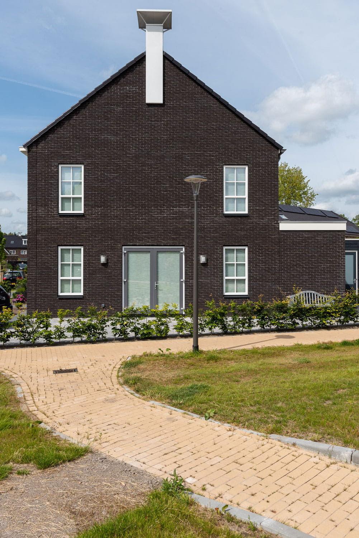 Zijgevel van een huis met donkere gevelsteen en licht pad ervoor