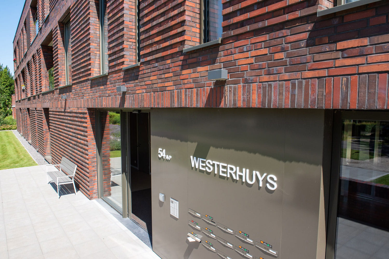 Detail van een muur met roodbruine steenstrips in langformaat en brievenbussen met de tekst Westerhuys