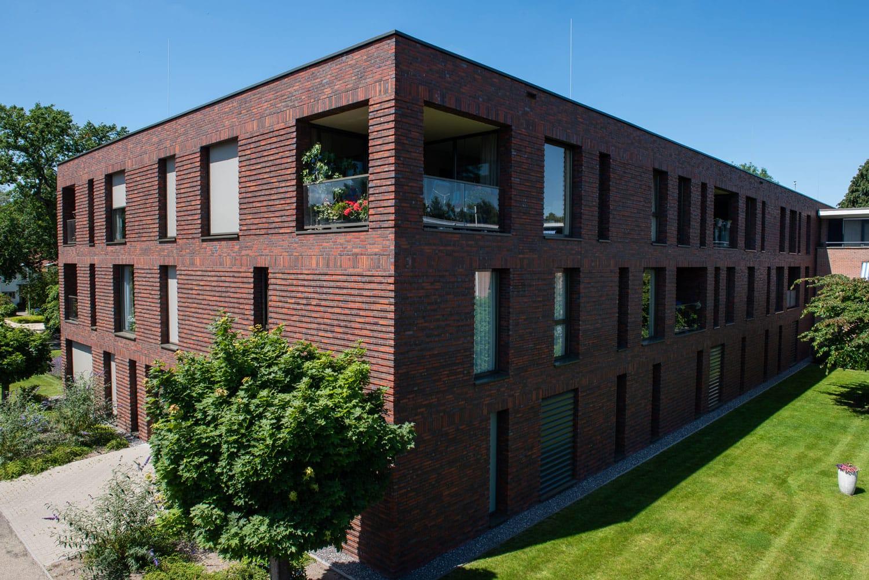 Zijaanzicht van een gebouw met roodbruine steenstrips en een tuin op de voorgrond