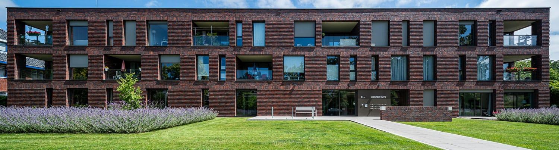 Vooraanzicht van een gebouw met roodbruine steenstrips en een tuin op de voorgrond