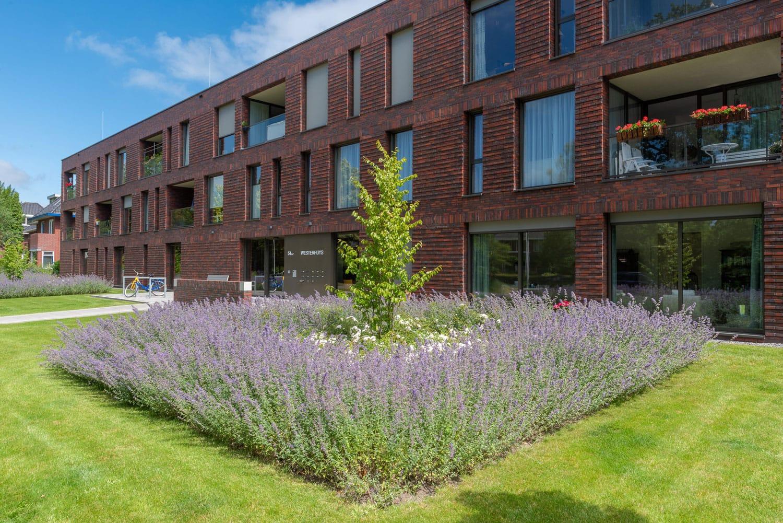 Zijaanzicht van een gebouw met veel ramen en een tuin op de voorgrond