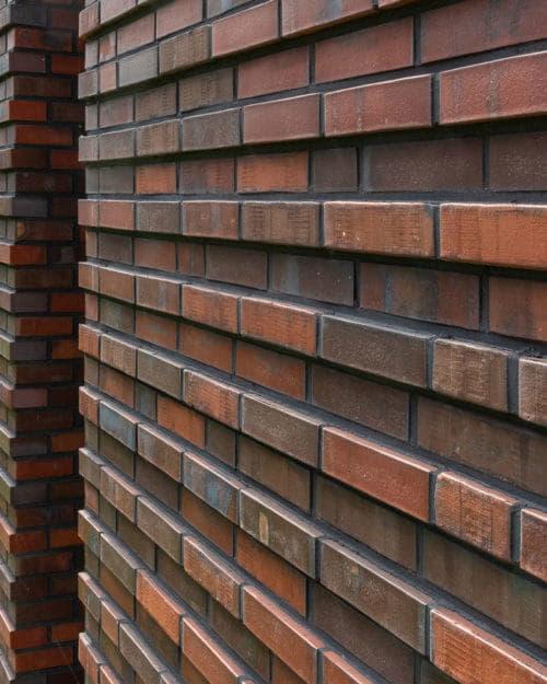 detail van een muur met roodbruine steenstrips in twee diktes