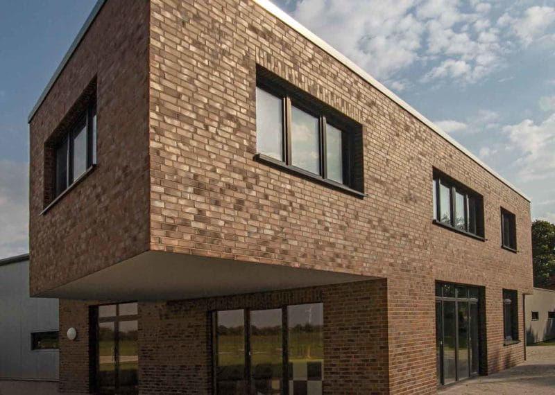 Hoek van een gebouw met bruine strips, ter illustratie van het gevelsysteem A-Brick