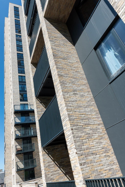 Zijkant van een toren met hoge muren met lichte bakstenen en steenstrips en schaduwen