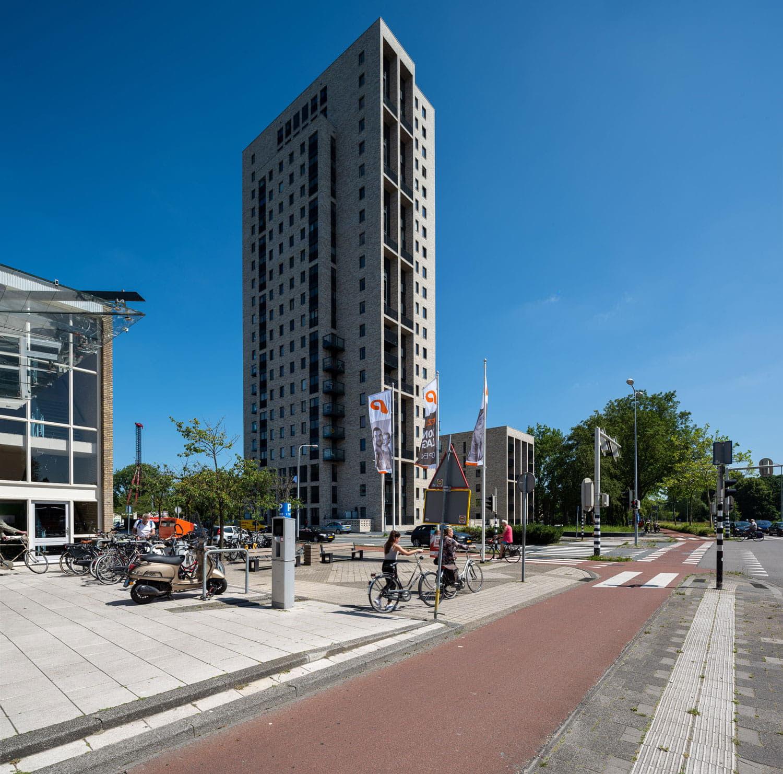 hoge toren met lichte gevelstenen en steentrips met op de voorgrond een fietspad en verkeer