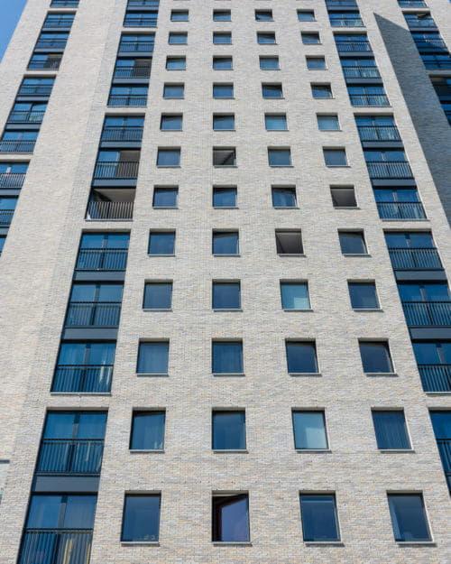 Een toren met lichte gevelstenen en ramen van onderen naar boven bekeken
