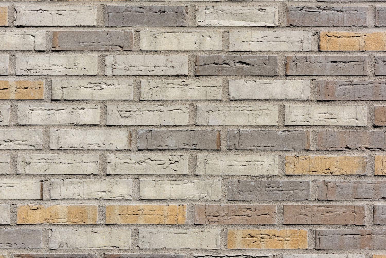 Een muur van dichtbij met gekleurde bakstenen