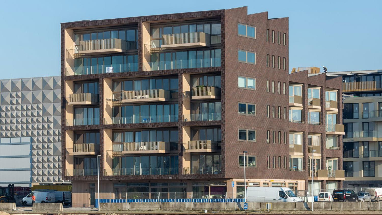 Gebouw met bruine steen en lichte balkons