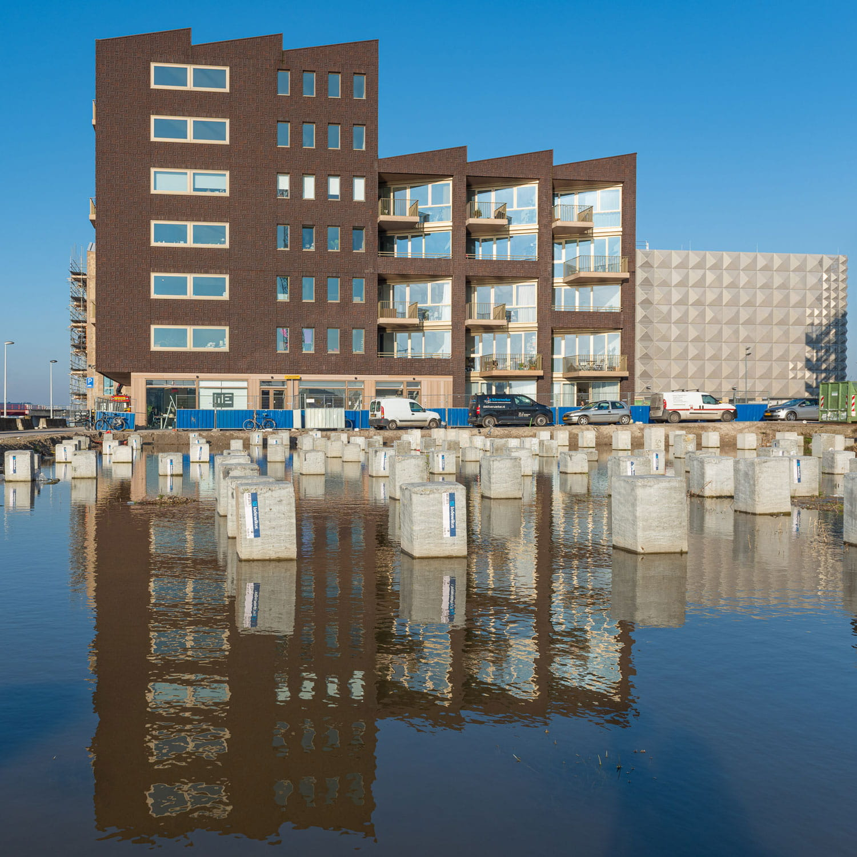 Een gebouw met bruine gevelstenen aan het water in Amsterdam