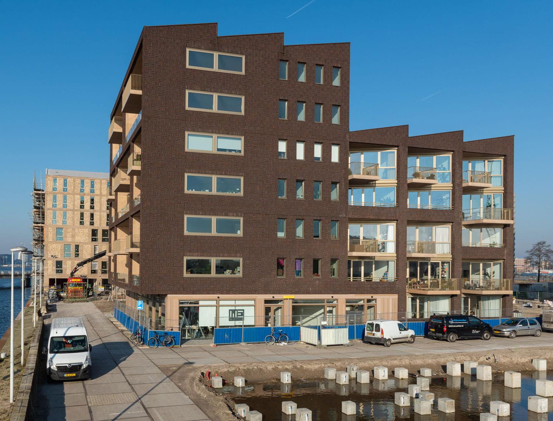Hoogbouw Dok7 in Amsterdam met donkerbruine stenen en lichte balkons