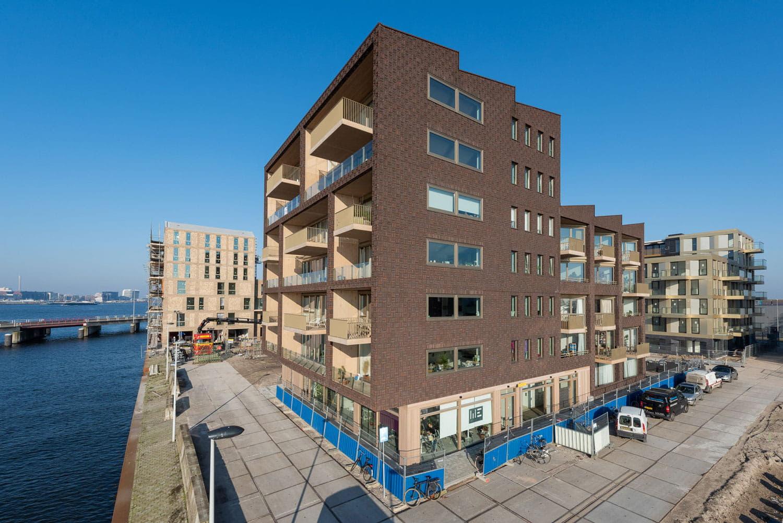 Hoogbouw van Dok7 met donkerbruine klampstenen en lichte balkons, met aan de voorkant water
