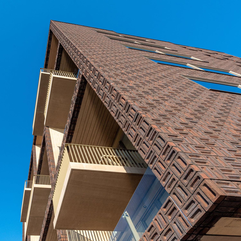 Gevel van Dok7 in Amsterdam, van bruine gevelstenen die klamp gemetseld zijn, van onderen bekeken