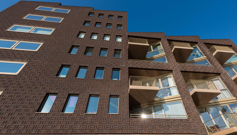Gebouw van dok7 met bruine gevelstenen die klamp gemetseld zijn en met lichte balkons, van onderen bekeken