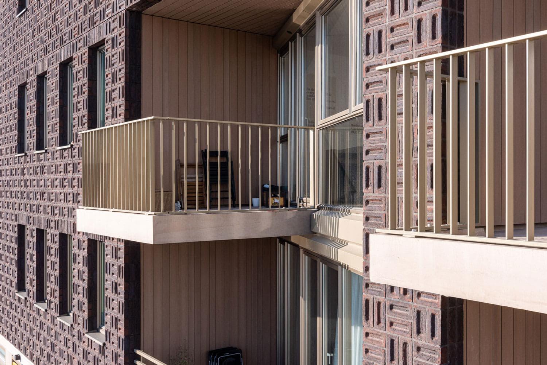 Detail van een bruine gevel van Dok7 met klamp metselwerk en twee balkons