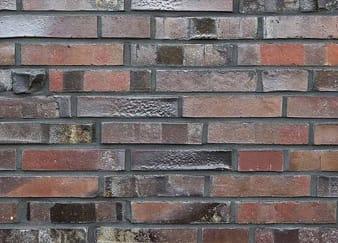Muur met verschillende kleuren roodbruine stenen