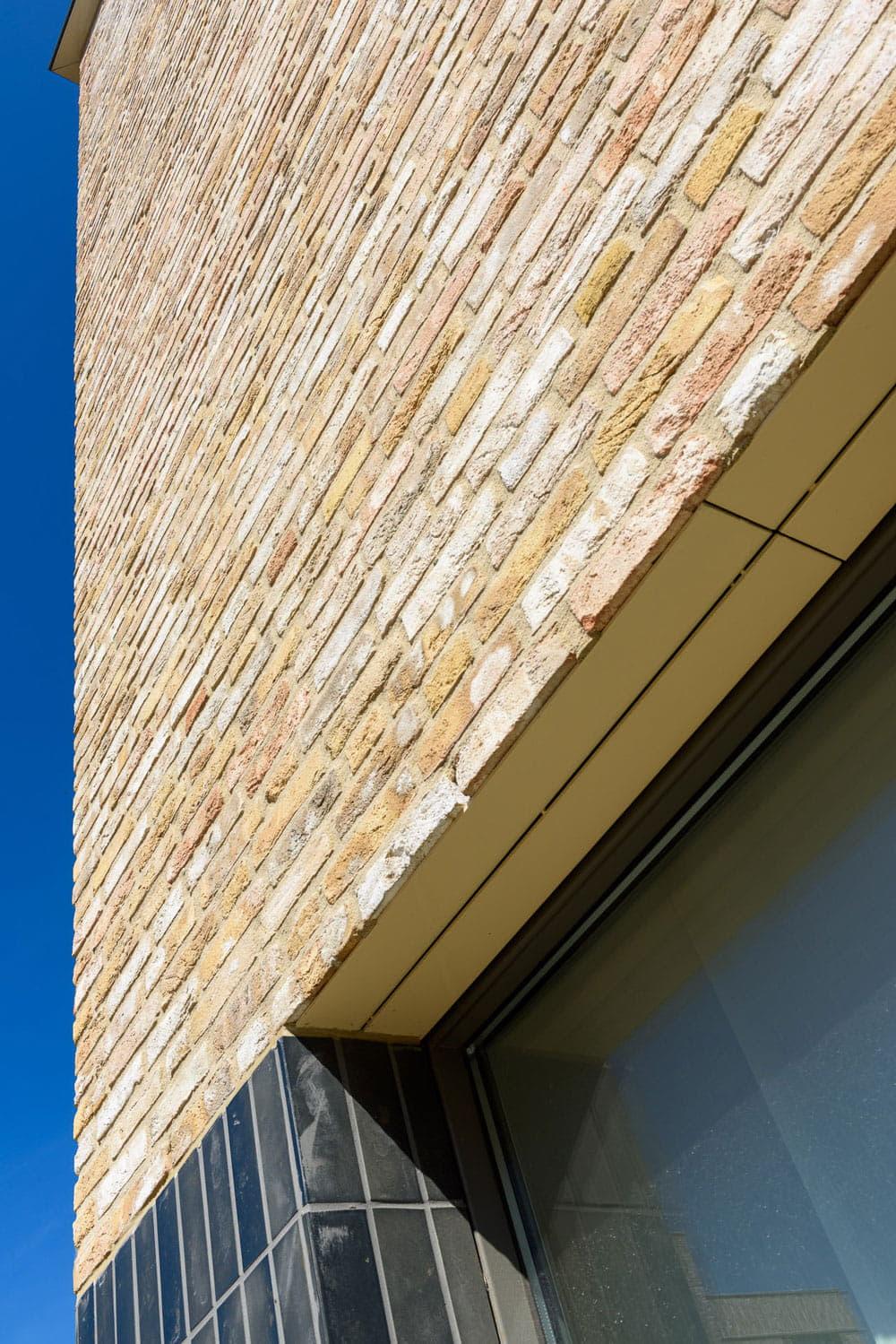 Strijp R detail van een gevel met lichte bakstenen en een negge met blauwe tegels van St Joris