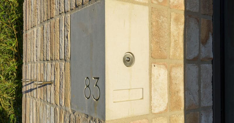 Betonnen huisnummer in een gevel met lichte bakstenen
