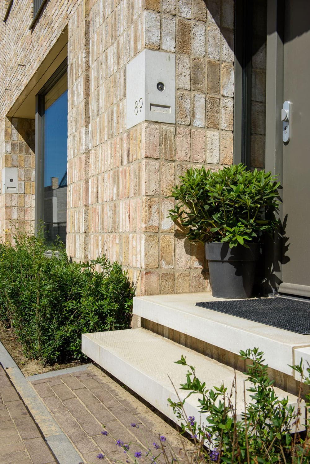 Strijp R entree van een woning met tredes, lichte bakstenen en betonnen huisnummers