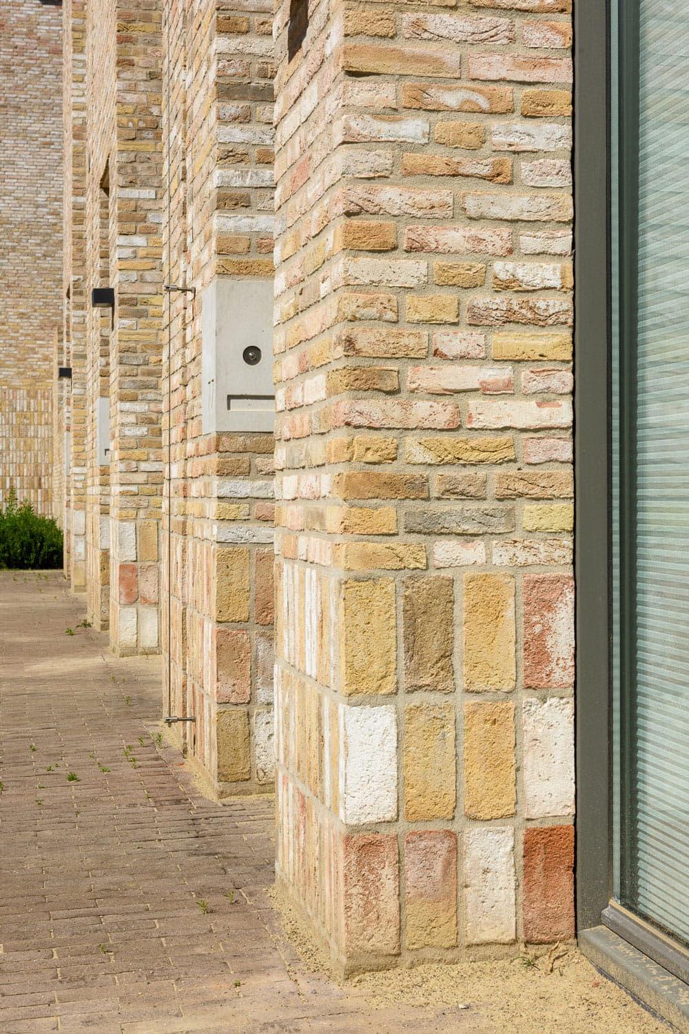 Strijp R pilaren met lichtgele steen met staand metselwerk en licht metselwerk aan de straat