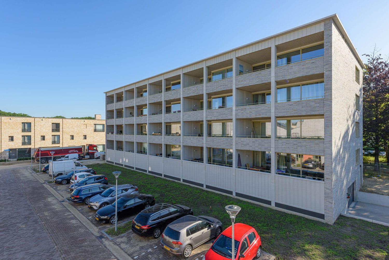 Strijp R appartementgebouw met lichte steen en parkeerplaats op voorgrond