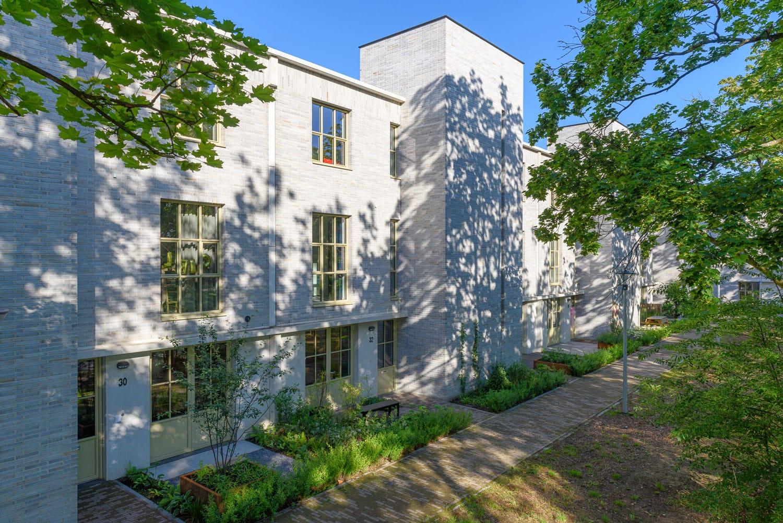Strijp R rij woningen van Hilberink Bosch architectenmet lichte steen en wandelpad ervoor