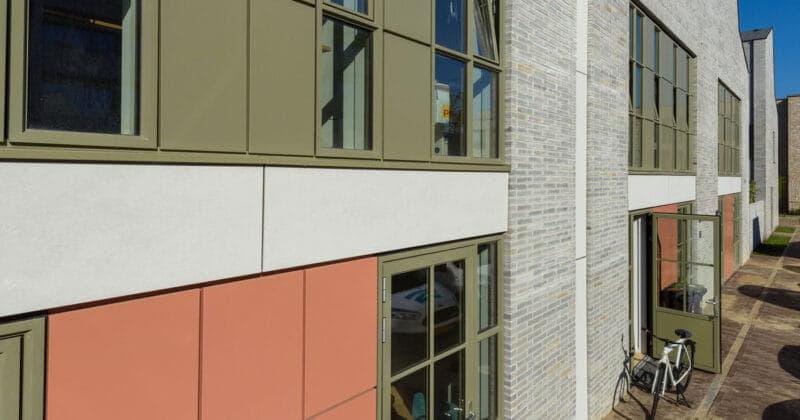 Strijp R zijgevel van rij sheddakwoningen met lichte grijze steen en industriele panelen