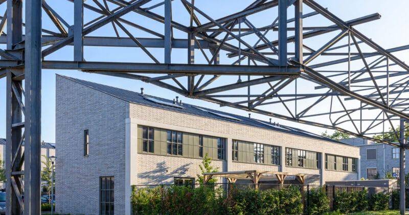 Strijp R woningen van Hilberink Bosch architecten met grijze steen en metalen constructie boven de weg van het oude philipsterrein