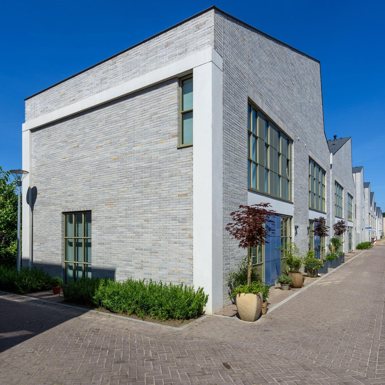 Strijp R hoek van een huis met sheddak en lichte steen en straat ervoor van Hilberink Bosch architecten