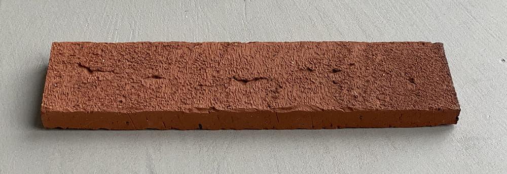 Steenstrip handstrich, bruin met een bezaagseld uiterlijk