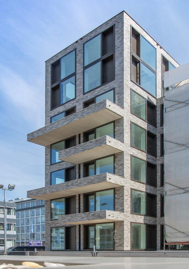Hoogbouw met balkons en een grijze steenstrip op het systeem van Sto