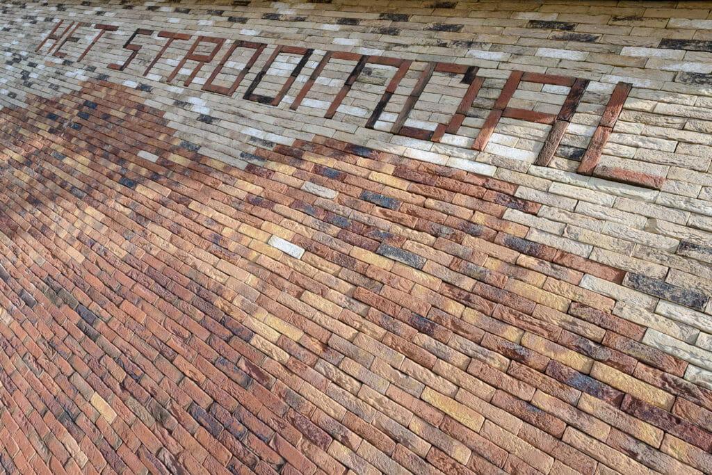 Detail van een gevel met steenstrips bij CKC het Stroomdal in Zuidlaren, met letters van de naam van de school