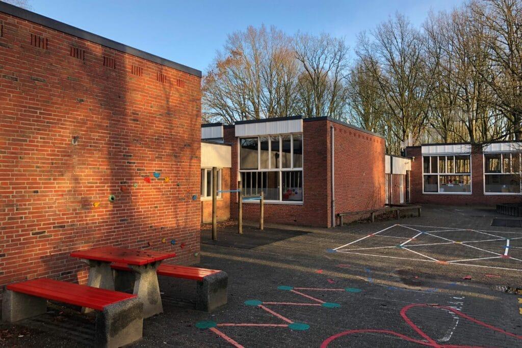 Schoolgebouw uit de jaren 70 met rode bakstenen