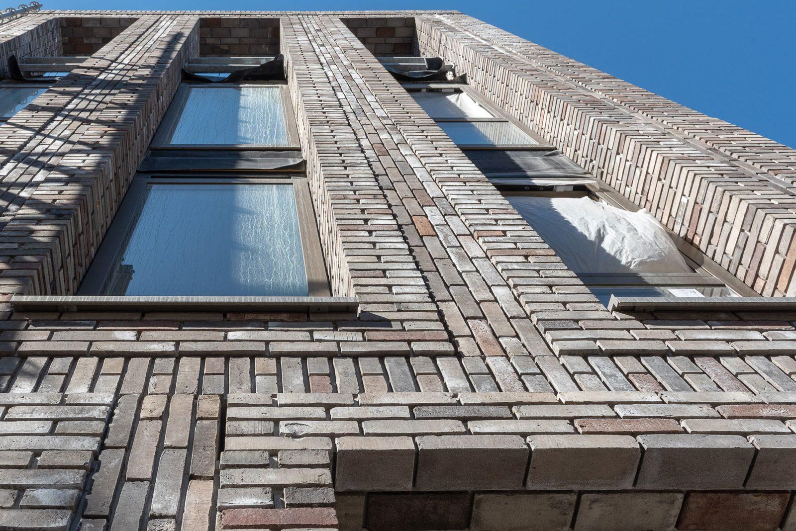 Een gebouw van onderen gezien, met uitsteken metselwerk en terugliggende stenen in lichte kleur